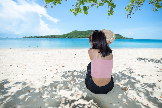 Back of asian woman tan skin wearing pink tank top and straw hat sitting on beach under tree. summer travel. relax.