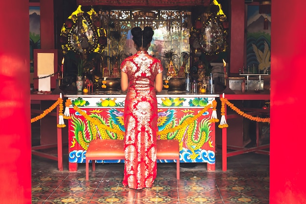 The back of an asian women wearing a red cheongsam standing in a shrine to pay respect to the gods