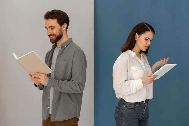 Back to back man with book and woman with tablet