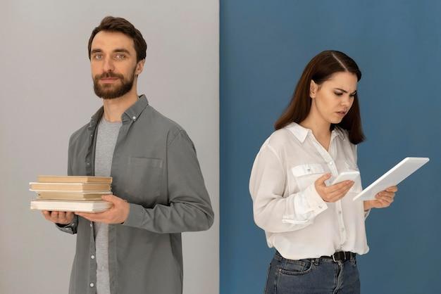Uomo schiena contro schiena con libro e donna con tablet