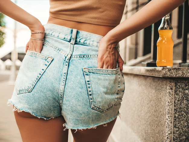 Back of beautiful sexy model in summer hipster jeans shorts clothes posing in the street
