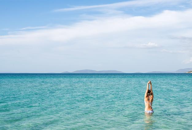 Back of beautiful woman wearing blue bikini standing in the water on mediterranean sea coast, cesme, ilica beach, turkey.