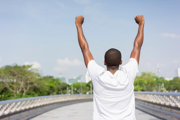 Back of black man enjoying city view and raising both hands.