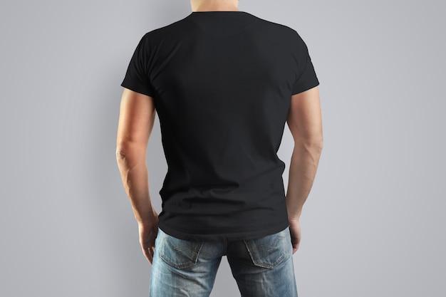 サンプルデザインの男性の背中の黒いシャツ。白い壁に孤立した男。
