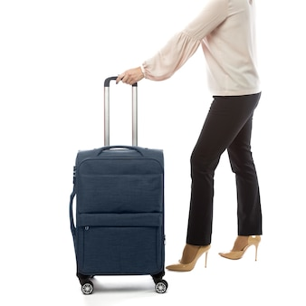 Back of businesswoman going in a travel and carry luggage