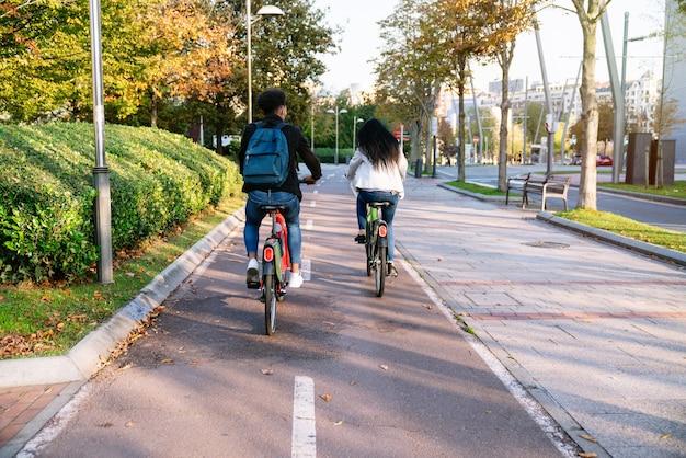 후면 카메라 두 젊은 남자와 일몰에 많은 나무가있는 아름다운 공원에서 공유 전기 자전거로 자전거 경로를 타는 여자