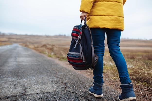 彼女の手にバックパックを持って孤独な道を歩いている女性の背面のクローズアップビュー。