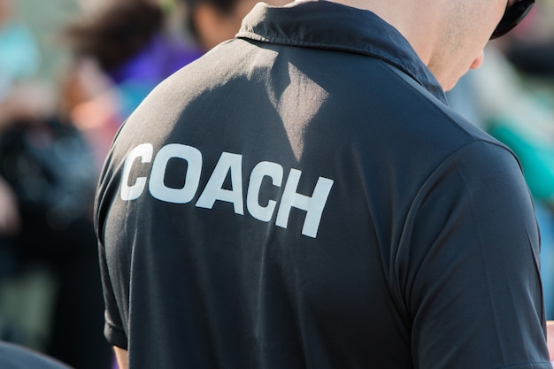 Back of a coach's black color shirt with the word coach written on
