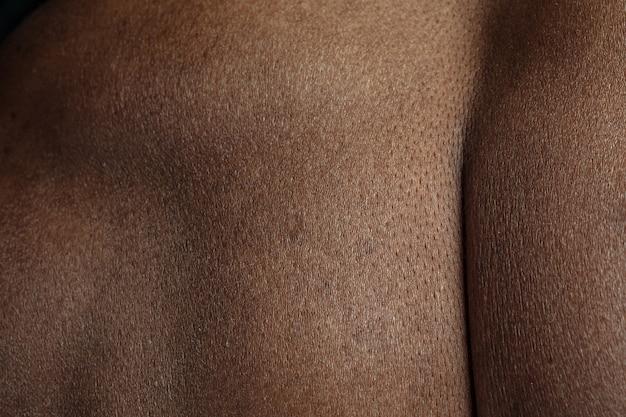 バック。人間の肌の詳細な質感。若いアフリカ系アメリカ人の男性の体のクローズアップショット。スキンケア、ボディケア、ヘルスケア、衛生、医学の概念。美しさと手入れの行き届いたように見えます。皮膚科。