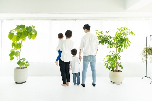 The back of a family standing side by side by the window