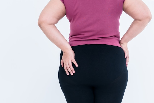 The back of a fat woman which puts the left hand on the hips which is large and full of excess fat