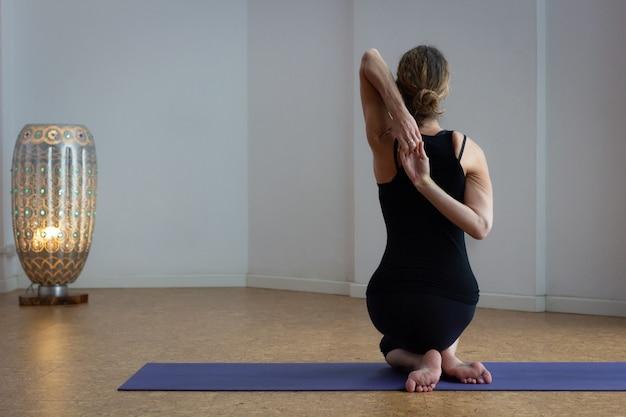 Back female yogi sitting in gomukhasana on mat with lamp on back fit woman practices yin yoga
