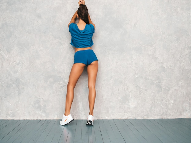Back of fitness woman in sports clothing looking confident.young female wearing sportswear. beautiful model with perfect tanned body.female posing in studio near gray wall