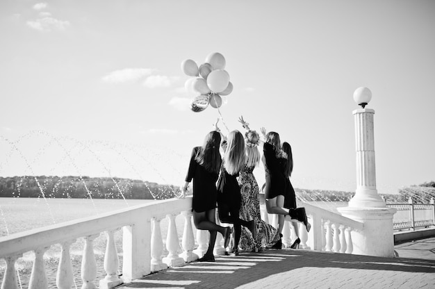 Back of five girls wear on black with balloons at hen party against lake.