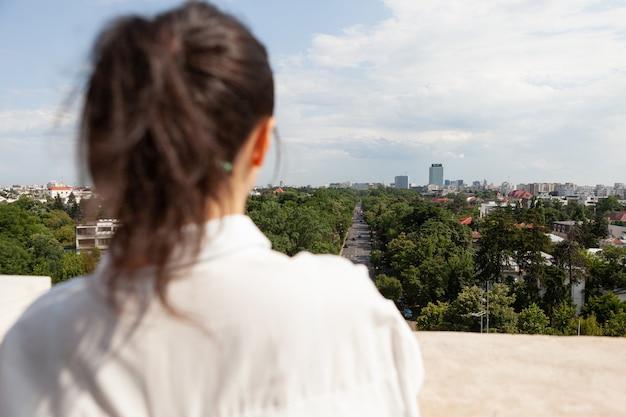 大都市のパノラマビューを見ている女性の後ろの正面