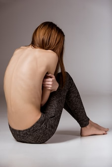 Back of girl with anorexia, clearly visible spine and ribs.
