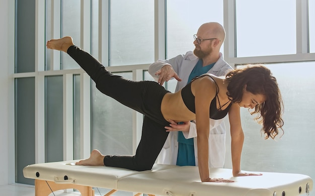 背中の健康女の子は現代のリハビリテーションで身体機能を回復する背中の運動を行います...