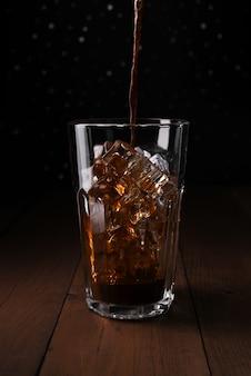 氷をグラスに注ぐアイスコーヒーをバックアップします。木のテーブルのガラス。背景のボケ味をバックアップします。透明なガラスのアイスコーヒー。