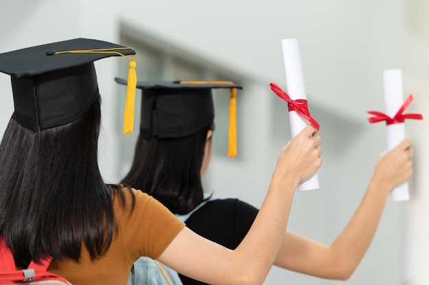 The back image of a female college student graduates wearing a black hat yellow tassel