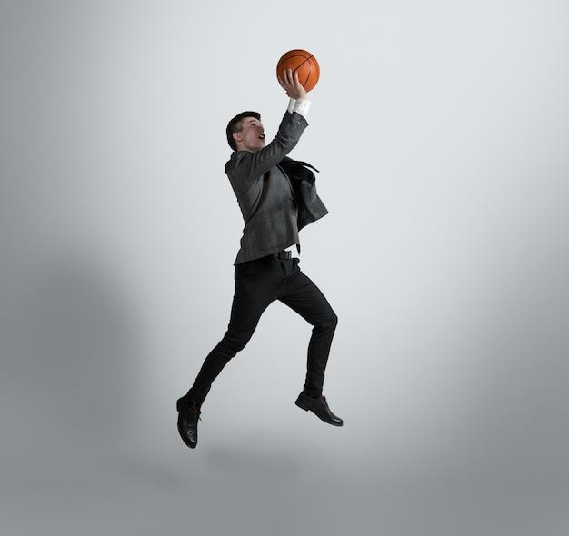 大学に戻って-スポーツスターになるのに遅すぎることはありません。オフィスの服を着た男は灰色の壁にバスケットボールで訓練します。動いている、行動しているビジネスマンの異常な外観。スポーツ、健康的なライフスタイル。