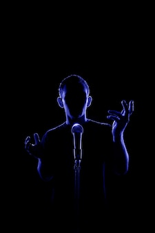 Back lit view of a faceless man talking or singing to a microphone