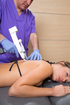 Back lumbar mesotherapy gun doctor with woman patient