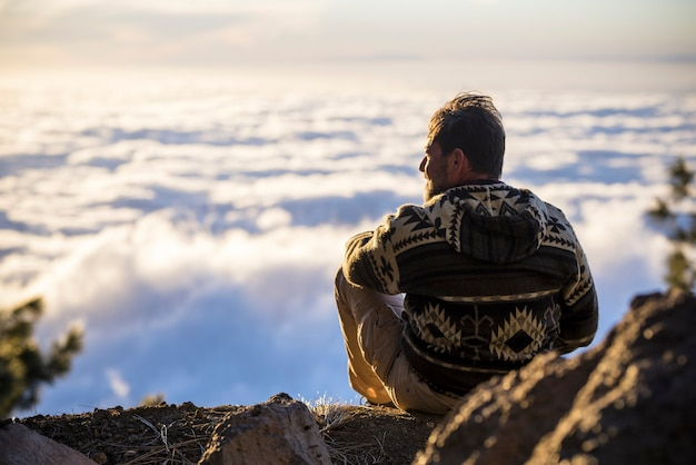 Back of man relaxing and admiring scenic cloudscape from mountain top. hiker admiring stunning cloudy sky from hill top. tourist taking a break and admiring breathtaking scenery from mountain peak.