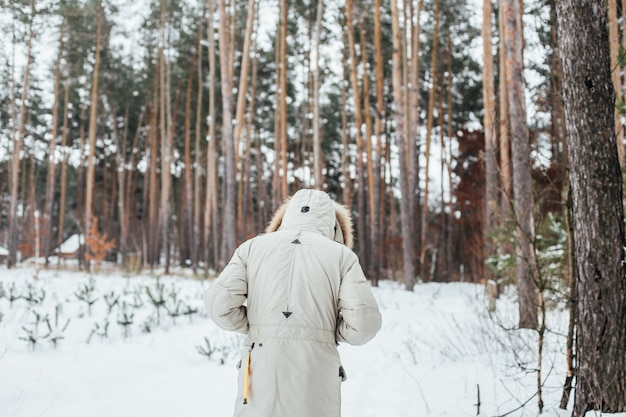 Back of man in winter coat walk into snow forest