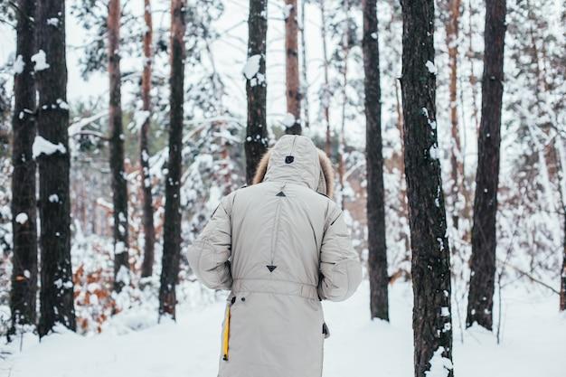 Retro dell'uomo in cappotto invernale a piedi nella foresta di neve