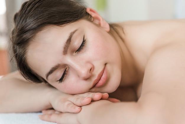 Массаж спины для молодой женщины в спа салоне, лицо крупным планом