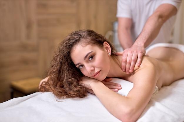 Массаж спины для молодой женщины в современном спа-салоне восстановление мышц после физических упражнений оздоровительное лечение спины спортивный массаж