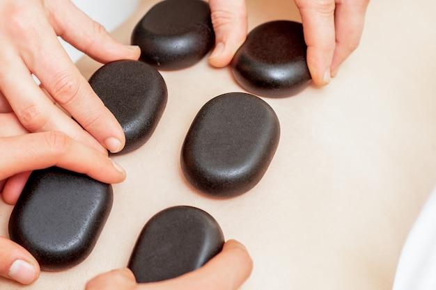 남성 마사지 치료사가 검은 뜨거운 돌을 가진 여성의 등 마사지.