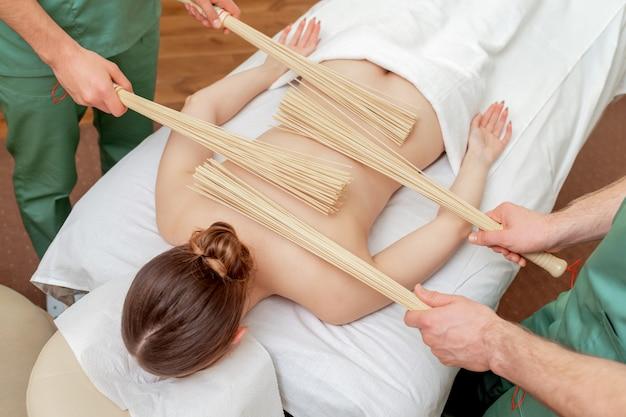Массаж спины с бамбуковыми вениками в четыре руки.