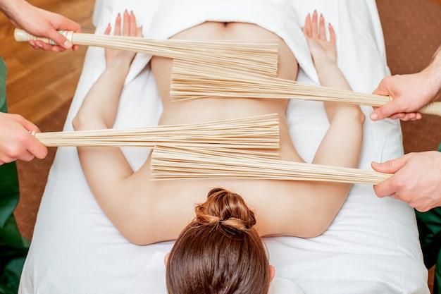 Массаж спины с бамбуковыми вениками.
