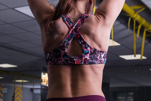 ジムで美しい女性の体の背中の筋肉。