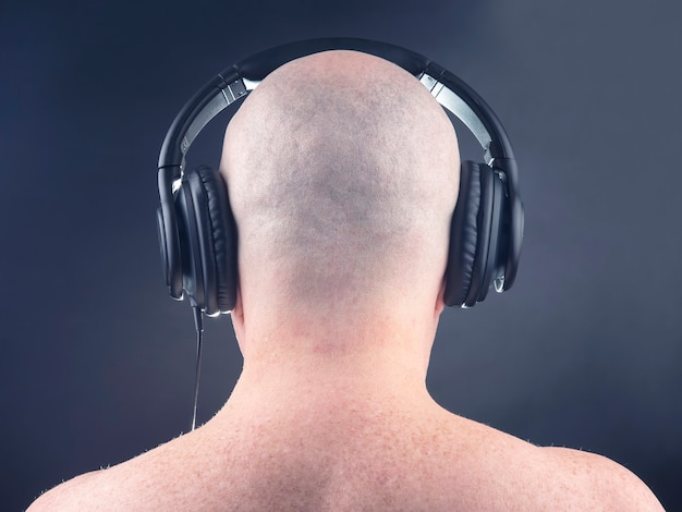 Back of a naked man listening to music with headphones on a dark background