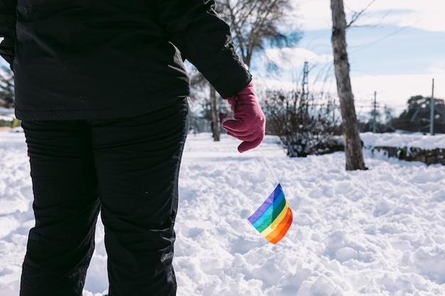 Спина лесбиянки в заснеженной местности держит радужный флаг лгбт