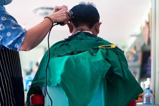 美容院で髪を切る男の背中