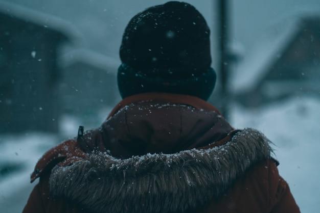 Спина мужчины в пальто с капюшоном и шапке зимой