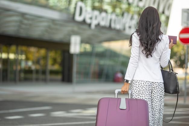 夏の日に空港の出発ホールに荷物を引っ張る女性の背中。
