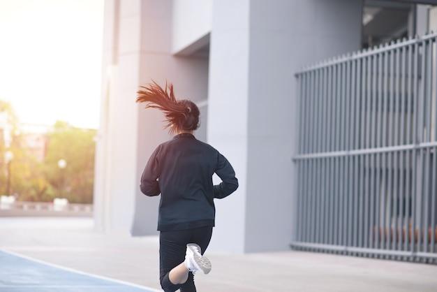 Задняя часть азиатского красивого черного костюма молодой женщины с счастливым бегом или бегом на беговой дорожке.