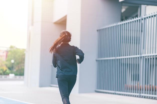 Задняя часть азиатского красивого черного костюма молодой женщины с счастливым бегом или бегом на голубой беговой дорожке.
