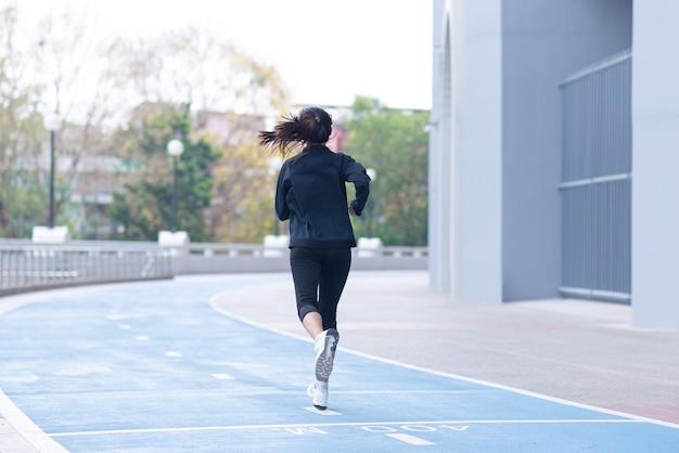 Задняя часть азиатского черного костюма молодой женщины с счастливым бегом или бегом на беговой дорожке.