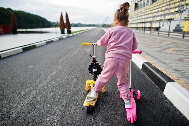 ピンクのスポーツスーツを着た女の赤ちゃんの背中は2台のスクーターに乗っています。