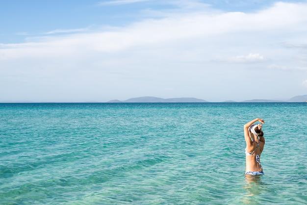 地中海沿岸、チェシメ、イリカビーチ、トルコの水に立っている青いビキニを着て美しい女性の裏。