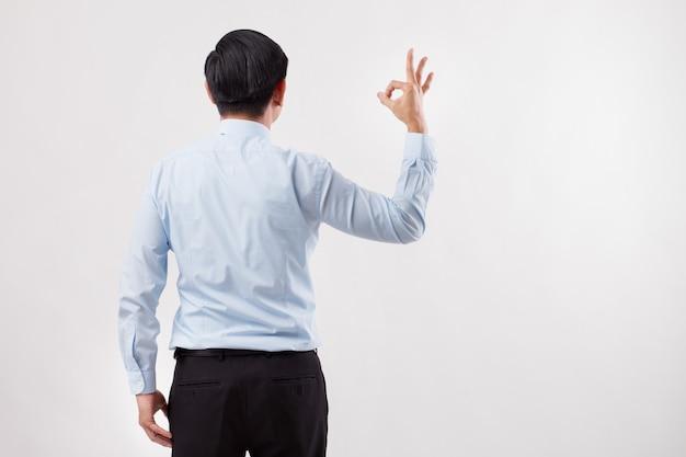 Спина делового человека, указывая знак руки ок на пустое пространство