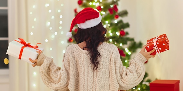 Задняя часть рождества санта женщина держит подарочные коробки с подарками дома возле елки