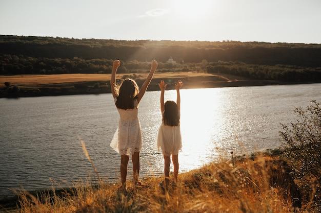Спина милых двух девочек-подростков в белых платьях с поднятыми руками