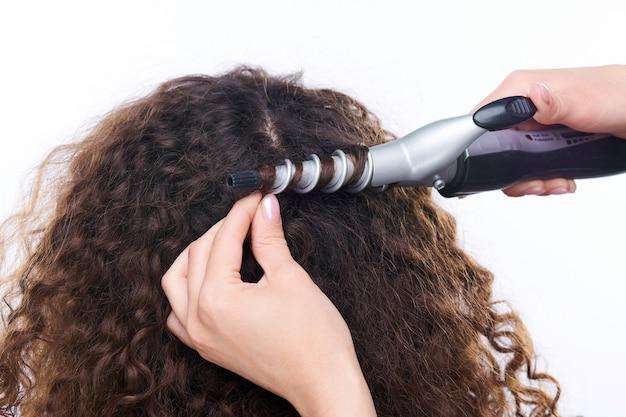 Затылок молодой брюнетки с длинными темными волосами, завитыми с помощью электрического устройства, парикмахер на белом
