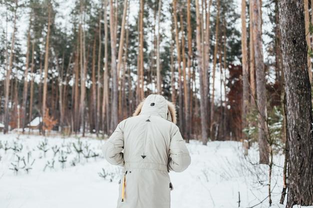冬のコートを着た男の背中が雪の森に入る